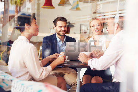 stock photo of men and women having a business meeting in a cafe