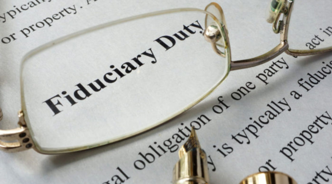 """a photo of a document with the words """"fiduciary duty"""" magnified by one the lenses of an eyeglass sitting on top of the document, even amid talks about the DOL Fiduciary Rule Changes"""