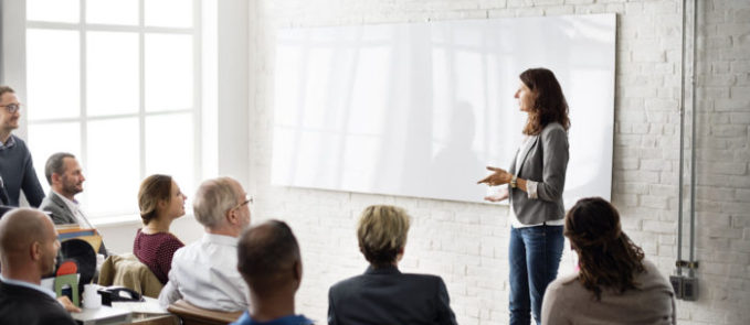 a photo of a group of workers seated in a classroom with a facilitator in front beside an empty whiteboard amid the reality that opportunities for education and training in the workplace is beneficial