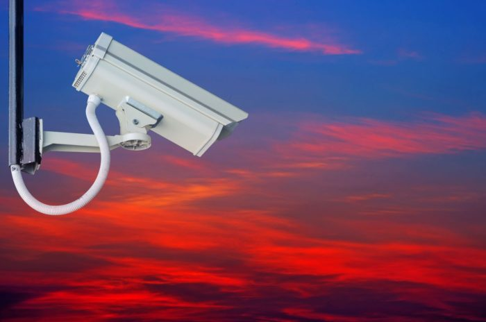 a photo of a surveillance camera with a background of a dusk sky amid the discussion of utilizing a border security surveillance system