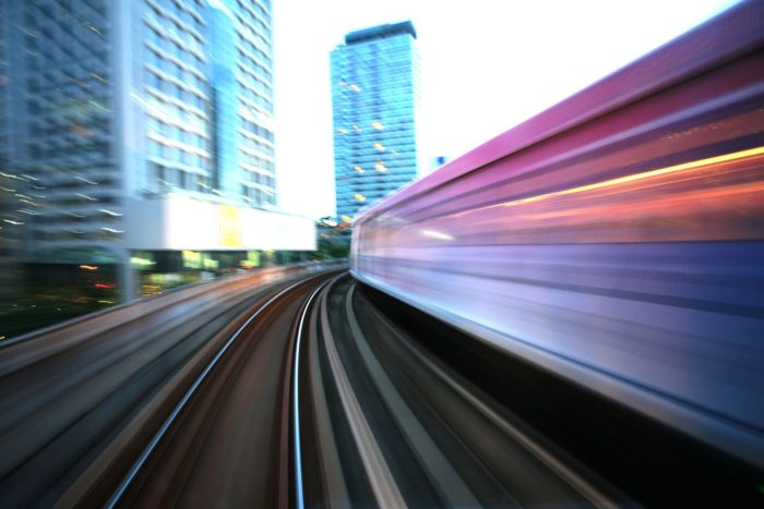 a photo of a train rider's view of a railway as the train lurches forward on its tracks amid the emergence of urban rail systems