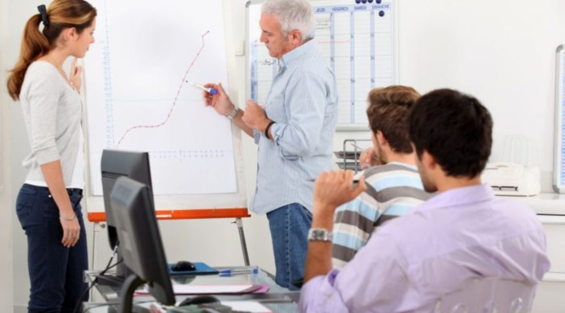 a photo of a teacher in front of a white chart training three students undergoing alternative education programs how to correctly make a graph