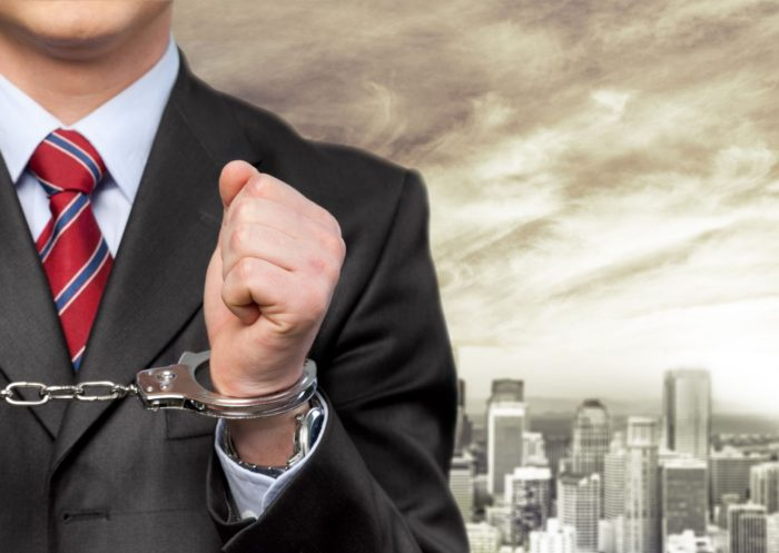 a photo of a businessman in handcuffs with a background of a city under dark clouds, thus depicting a crisis of overcriminalization
