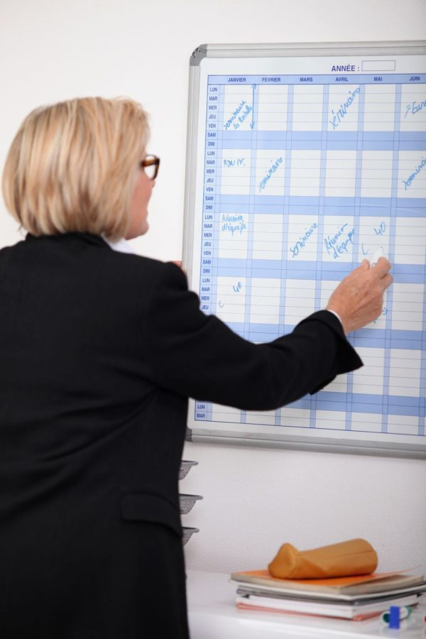 a photo of a businesswoman writing on a wall calendar with a marker, which directs a person's attention to the conveniences of using the Magic Calendar