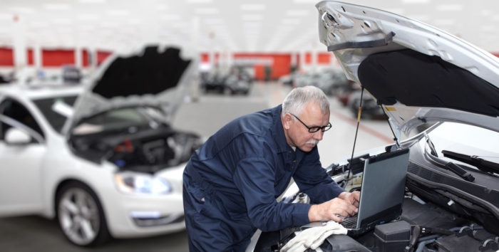 a photo of an engineer looking into tapping on the power of big data and transportation as he works on his laptop sitting on top of an open hood of a car's engine in an auto shop