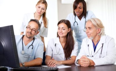 team of doctors and nurses sitting together around a computer