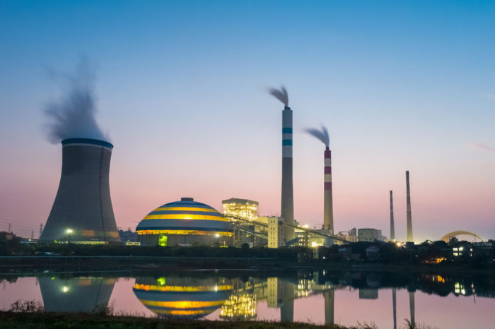 a photo of a plant or factory that uses fossl fuels and that's near a lake amid the current global coal consumption forecast