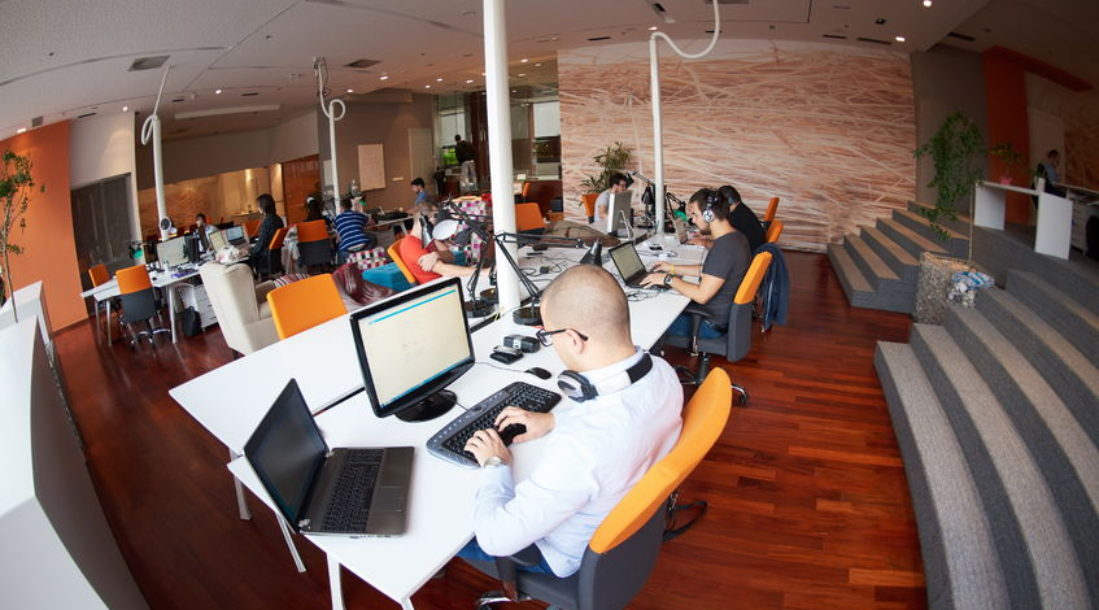 a photo with a fish's eye view of an open office with a white male in a polo (at the center of the image)working in front of a computer that tells him the current data on EverFi investing situation