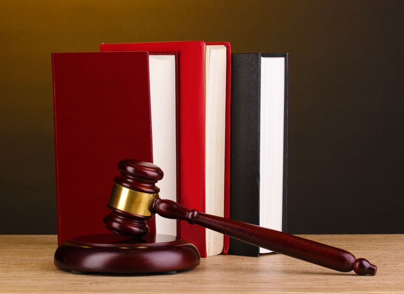 a photo of a judge's gavel and striking block positioned beside three books on a wooden desk amid the reality of mandatory minimum sentencing laws
