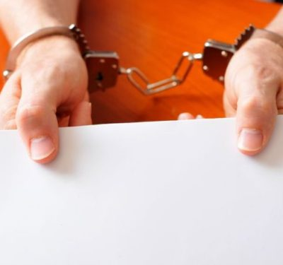 an inmate's handcuffed hands holding out a blank paper as people recognize the benefits of education in prisons