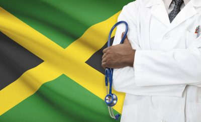 Doctor in front of a Jamaican Flag.