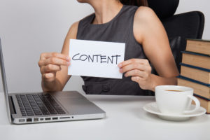 woman holding content sign sitting at computer desk with coffee