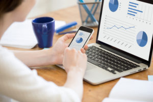 smartphone syncing email analytics with laptop on desk