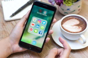 two hands holding a smartphone displaying social media icons next to coffee mug