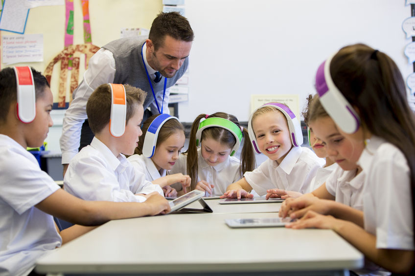 students in the classroom wearing colorful headphones