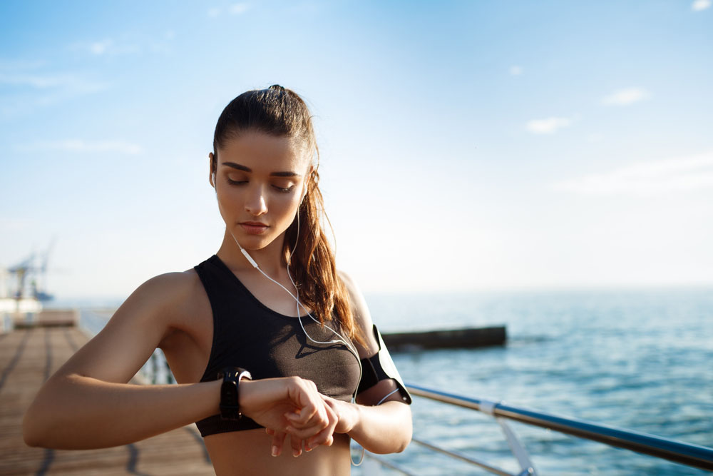 a photo of a girl looking at her Apple watch by the ocean even amid the existence of Apple's secret fitness lab