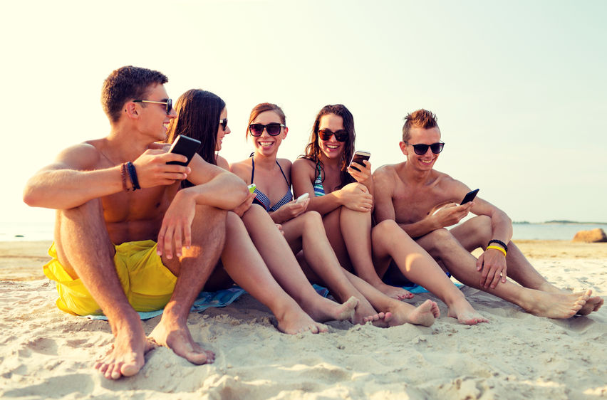 teens sitting together on the beach smiling