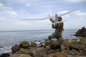 Man in military fatigues, casting a drone over water.