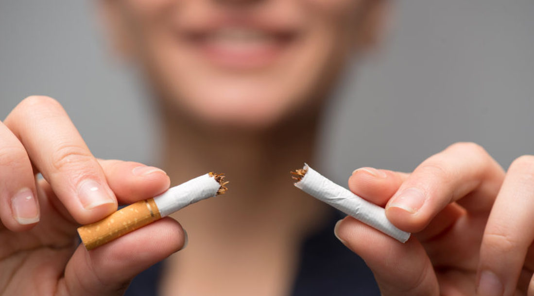 a photo of a woman breaking a cigarette in two because of the bold impact of the SmartQuit app
