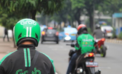 Motorcycle delivery with grab logo.