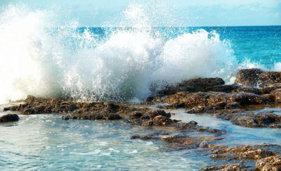a photo of waves breaking on rocks with a background of the Pacific Ocean amid the reality of Atmocean and its System for Smart Desalination of Seawater for Drinking