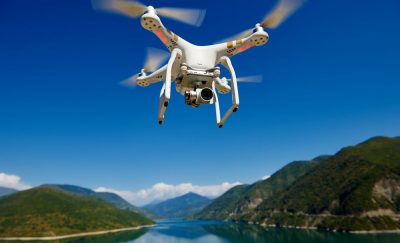 Beyond line of Sight Drone flies over lake and mountains.