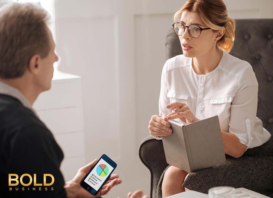a photo of a therapist holding a notebook and and male patient holding a phone while speaking to each other amid the need to jumpstart the development of mental health digital technology
