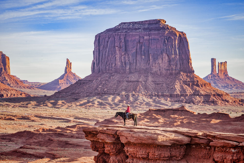 Image of an Navajo on a horse with buttes.