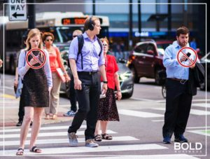 People textng and walking on a busy street. Ban texting while walking law was implemented