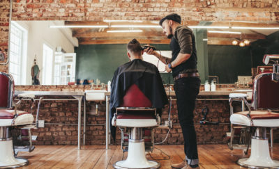 a photo of a barber shaving the head of a man's head inside a stylish barber shop while scientists discover a stem cell hair growth cure