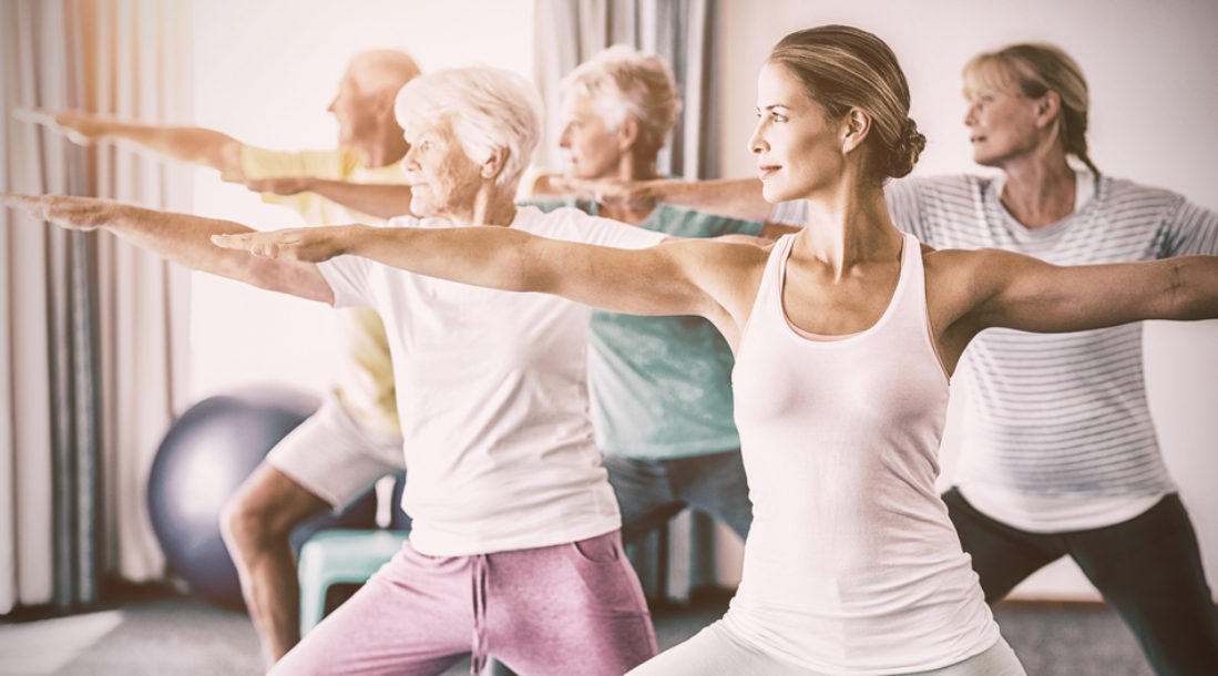 a photo of elderly men and women doing yoga stretches as instructed by a young woman in a class amid discussions about healthcare for senior citizens