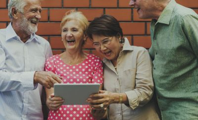 a photo of two elderly men and two elderly women laughing while looking at a tablet opened to the mobile app created by Masako Wakamiya