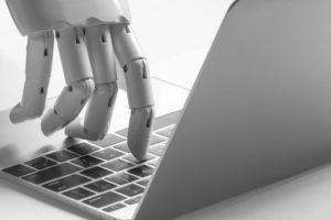 AI robot hand typing on laptop keyboard image