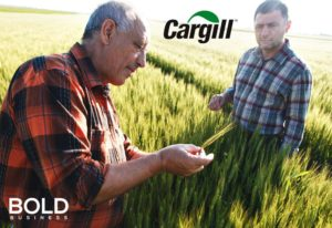 Farmer in field with Cargill logo.