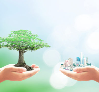 Children holding a tiny tree and a tiny city in their hands.