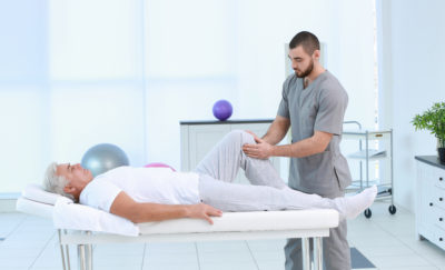 physical therapist manipulates patient's knee