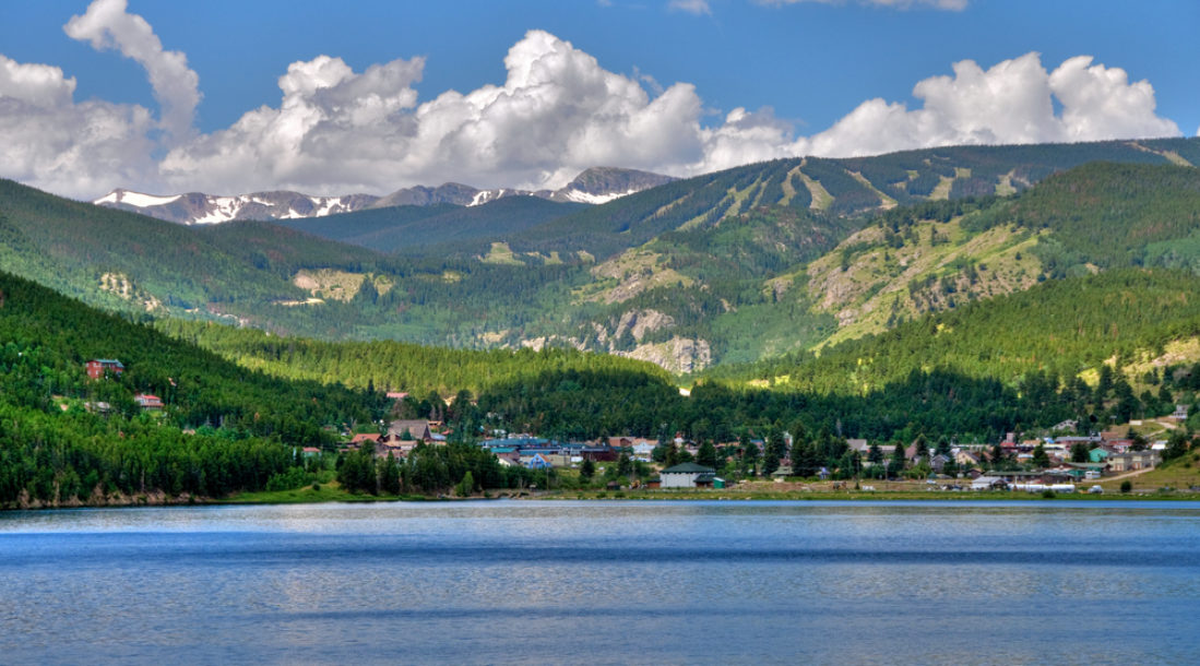 a photo of a mountain town and a lake amid the details about renewable energy in Colorado