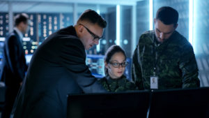 Military man and woman in uniform with man in suit at computer exploring cyber security blockchain technology.