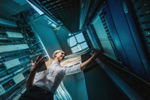 Woman in server room. Digital Divide Growing