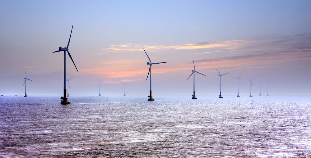 a photo of three wind turbines out in the open sea amid the joint offshore renewable energy project of China and the UK