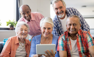 a photo of a group of seniors looking at a tablet that has their health records stored by StoriiCare