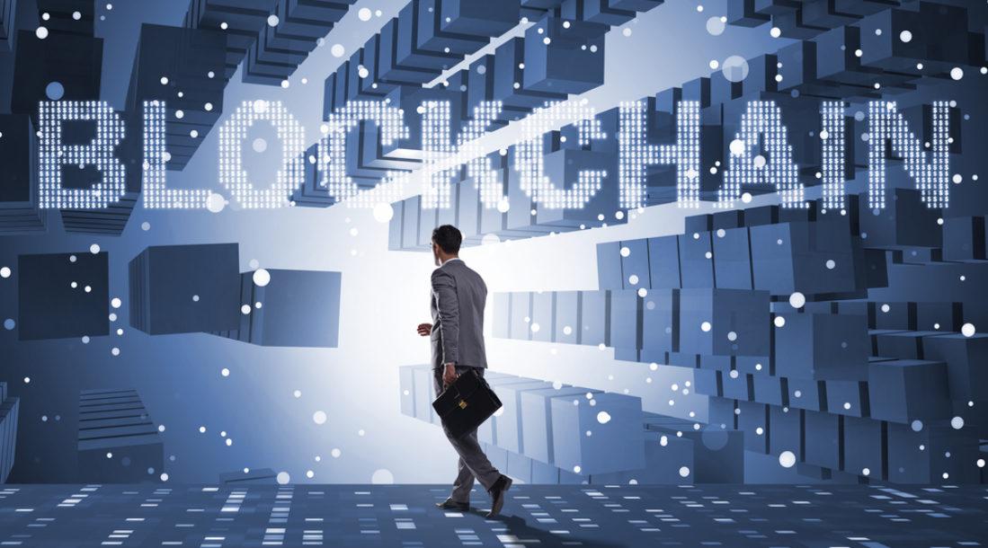 guy in futuristic hallway with blockchain above him