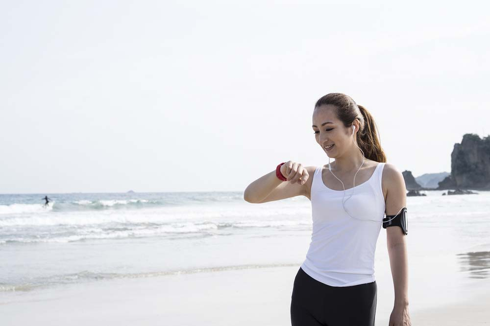 Woman with tech watch on beach.