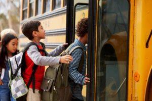 Kids getting on a school bus.