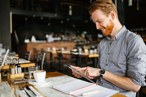 Man in cafe using tablet.