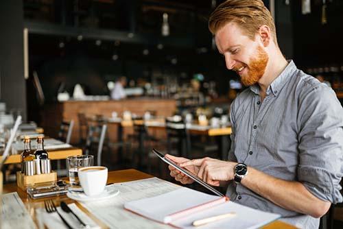 Man in cafe using digital food ordering system