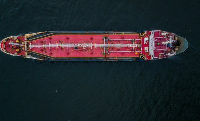 a photo showing an aerial view of an oil tanker amid the existence of bitumen pellets