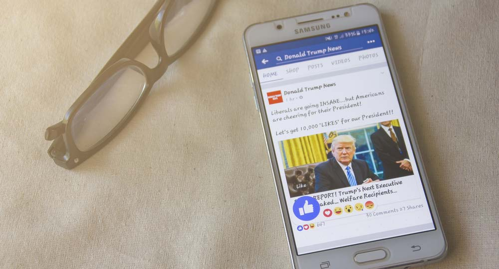 A phone with a Facebook news feed showing, The Trust Project is countering fake news!