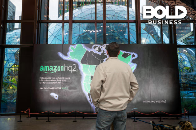 a photo of a man looking at a board showing a map of the United States with the finalist cities included in the Amazon HQ2 shortlist highlighted in green