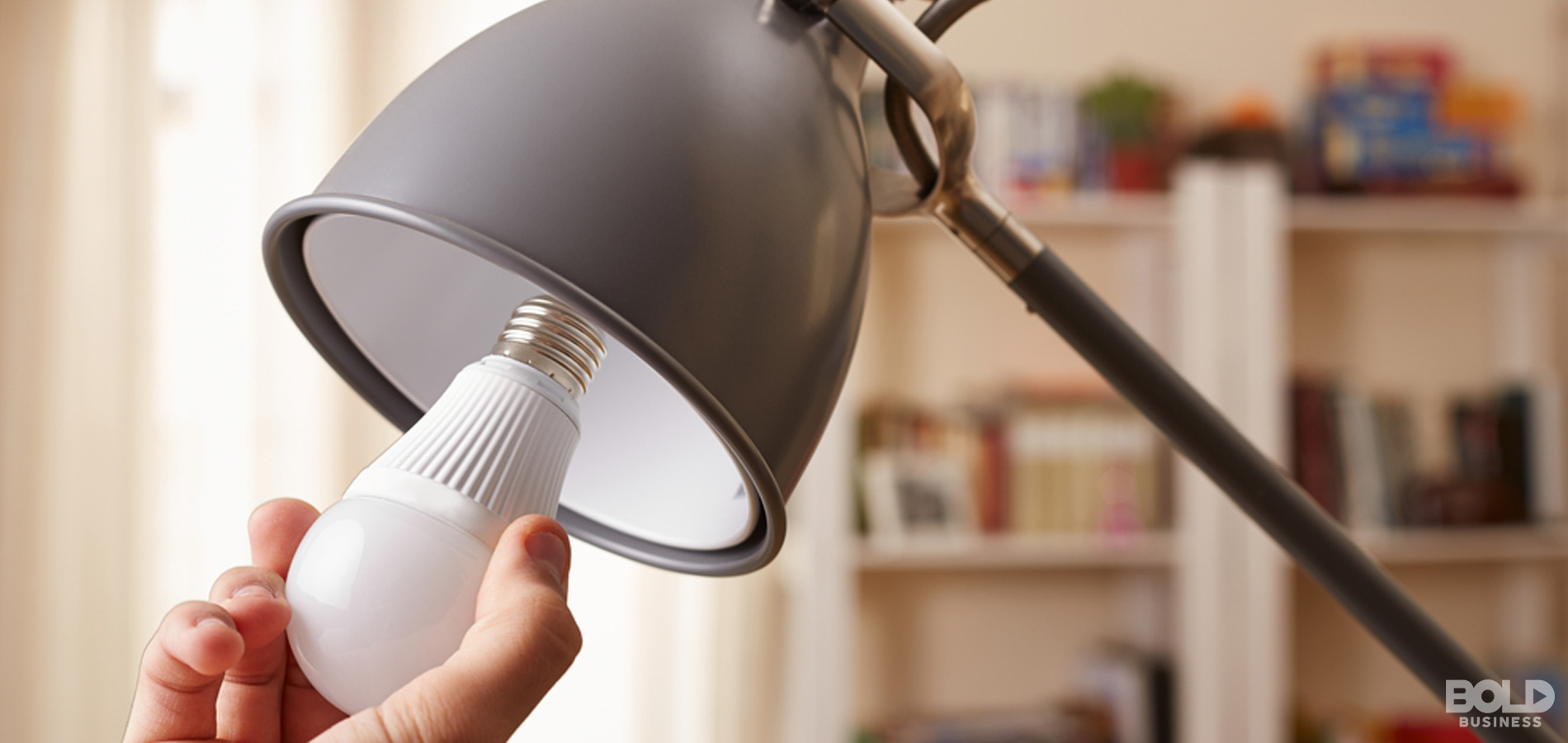 a photo of a lamp shade with its light bulb being removed by a hand in connection to the topic of LED light pollution